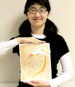 Phoebe Moh'14 poses with one of her favorite drawing of a bird. It is one of her largest works.