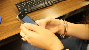 PHOTO ILLUSTRATION: A student uses an iPhone during class.  Students are becoming very attached to their phones.