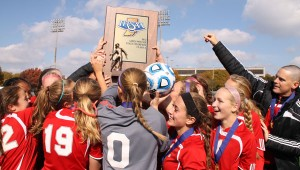 Making History: The girls' soccer team swarms around their trophy immediately after winning their game.  They are the first girls' soccer team in West Side history to win the state championship