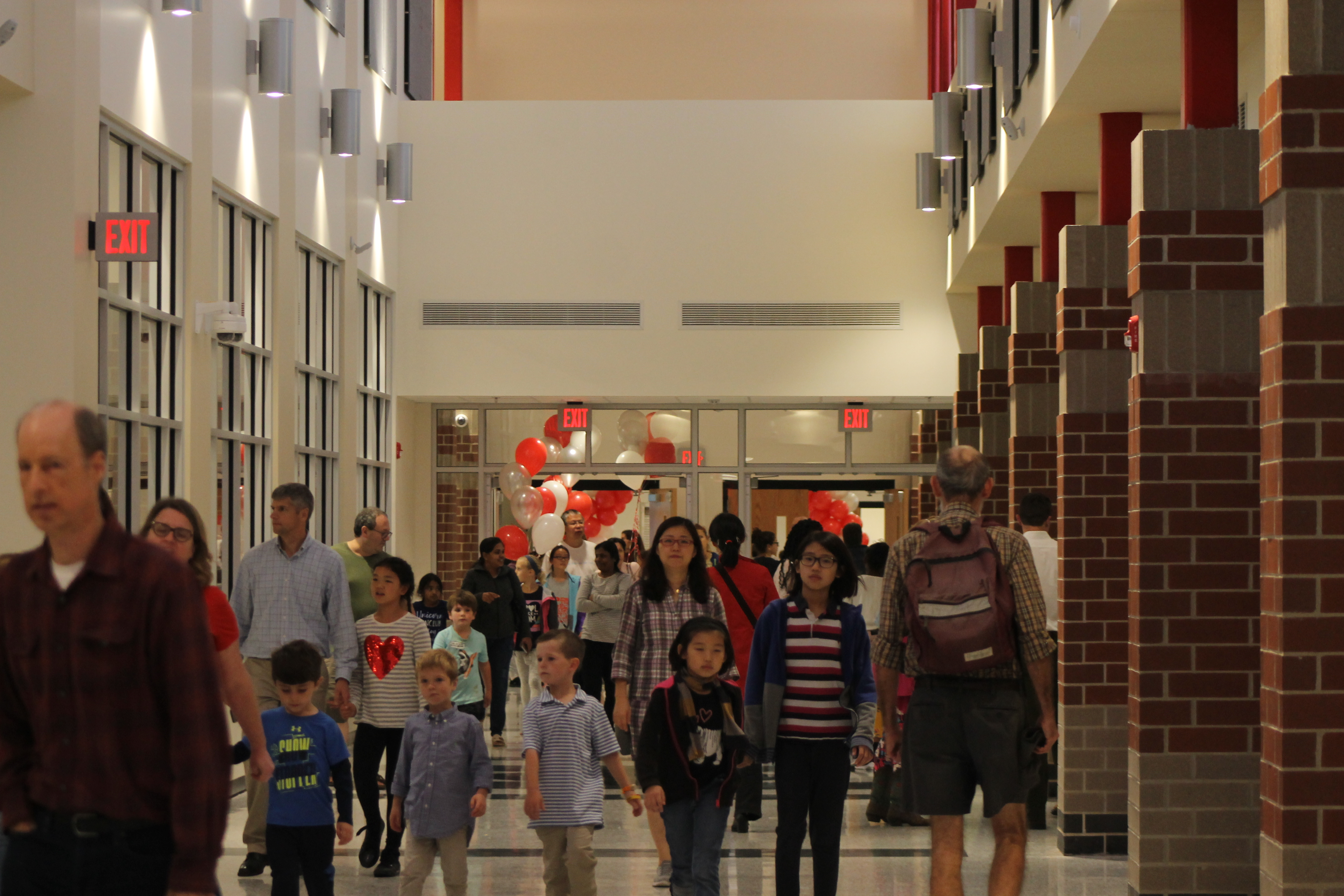 "A WALK DOWN THE HALLWAY: Guests tour down the  fascinating hallway that has been rumored to have cost a million dollar itself. ""The new school was very well designed and made me reminisce about the times that I was in Happy Hallow. The hallway especially impressed me because the high ceilings and colors and light made it a place to walk through and experience the school,"" said Ania Ahsan, a sophomore at WLHS."
